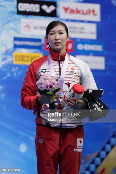 Gold medlist Rikako Ikee of Japan stands on the podium for the national anthem at the medal ceremony for the Women's 100m Butterfly Final on day...