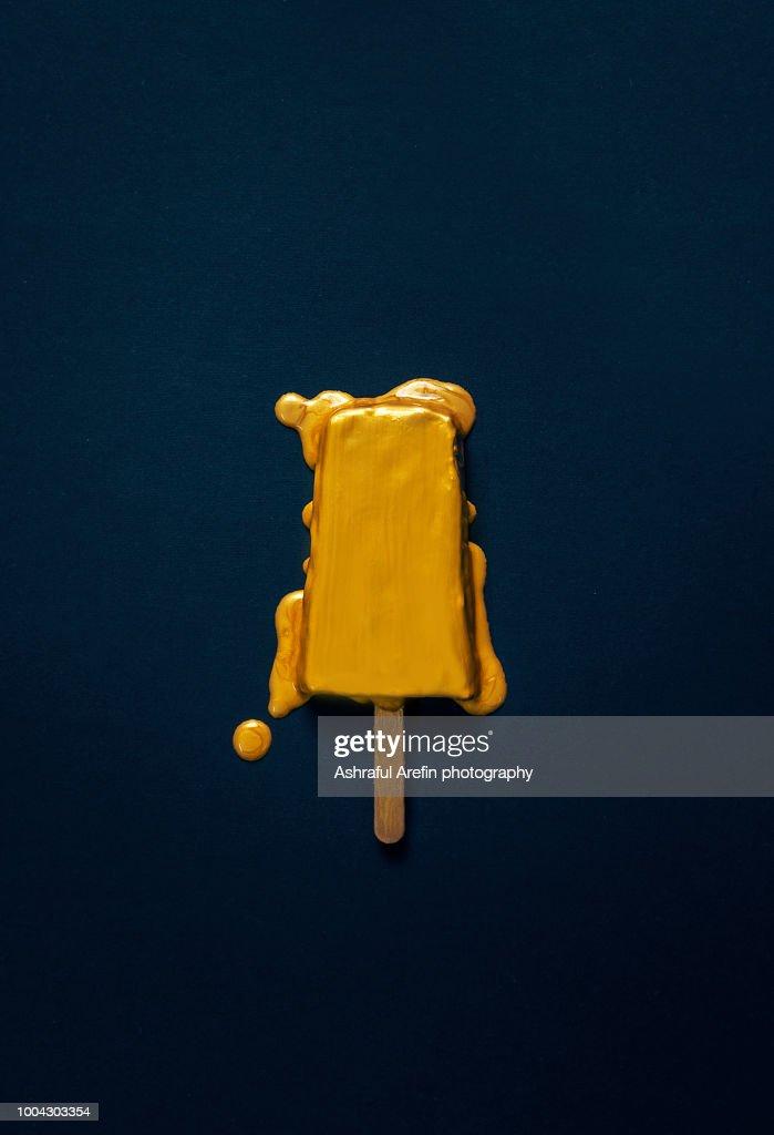 Gold melting popsicle : Stock Photo