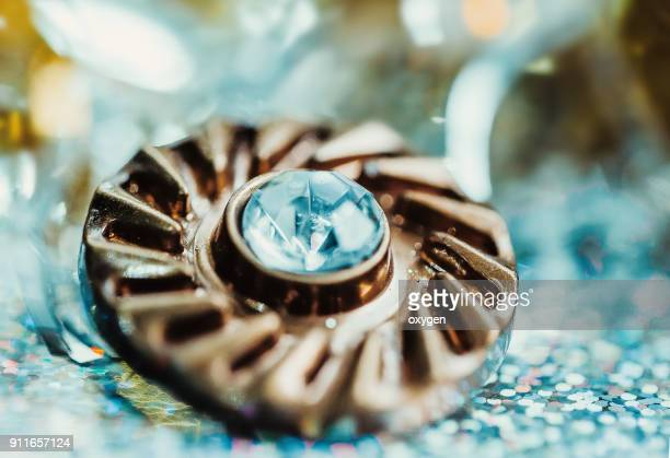 Gold metall button with cristal on bokeh background