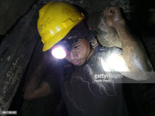 A gold miner carrying a sack of gravel containing small amounts of gold particles