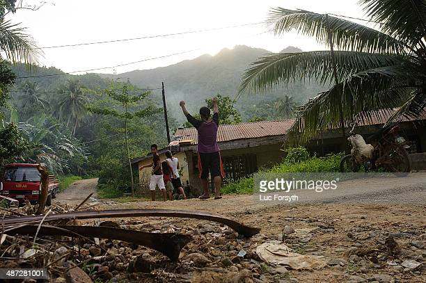 A gold miner celebrates the end of a work day as he walks towards his home on April 22 2014 in PinutAn Philippines Gold mining is the primary source...
