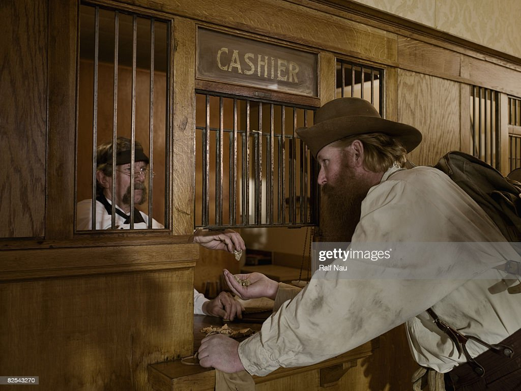 Gold miner selling gold to teller at bank : Stock Photo