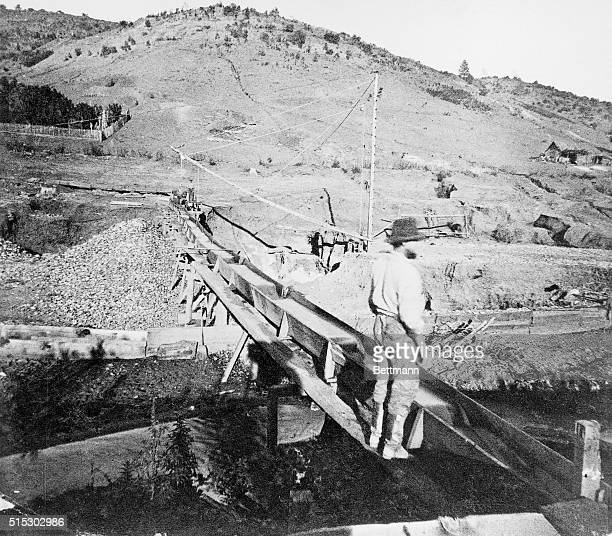 A gold miner stands on an aqueduct while placer mining at Brown's Flat in Tuolumne County California during the California Gold Rush
