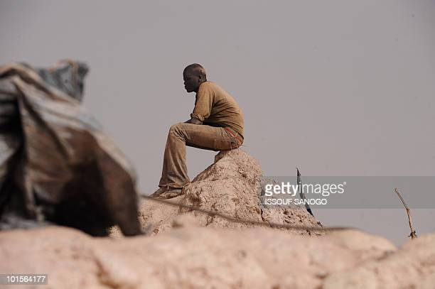 Gold miner takes a break after coming out of a hole where he was digging and looking for gold in Namisgma, the largest gold washing site in the...
