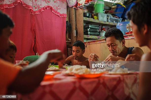 Gold miners and their family eat dinner together in a small house built near their mountainside camp. Many miners have homes in the nearby village of...