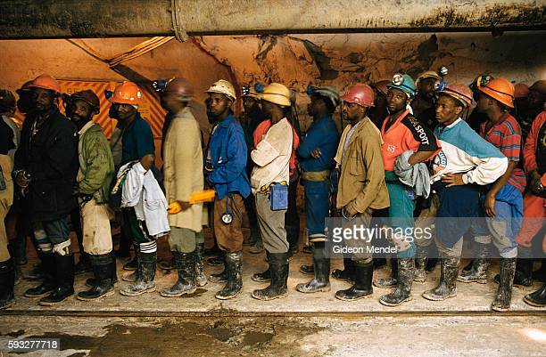 Gold miners at Great Noligwa mine queuing at the end of their shift to take the mine shaft lifts back to the surface An estimated 30% South African...