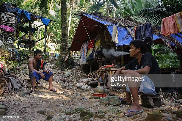 Gold miners smoke cigarettes and relax after a 10 hour day of working in the tunnels on April 22 2014 in PinutAn Philippines Gold mining is the...