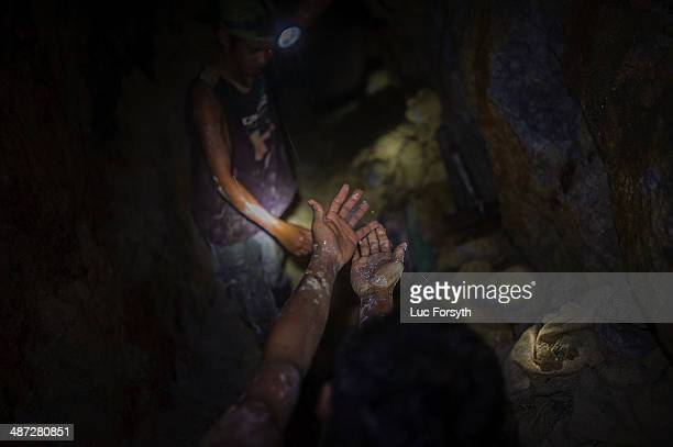 Gold miners wash their muddy hands in the dripwater falling from the ceiling of an active tunnel Water continuously leaks through the cracked stone...