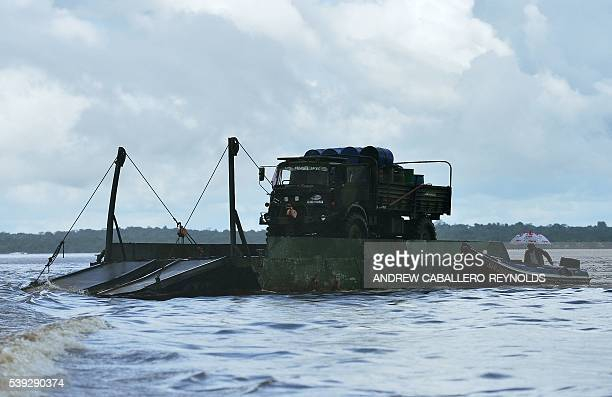A gold mining truck is pushed down the Mazaruni river by a smaller river boat near the town of Bartica Guyana on June 6 2016 Bartica is a town at the...