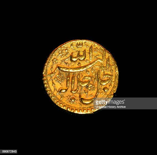 Gold Mughal coin of Emperor Akbar Agra 15561605 This gold coin carries ornate Persian inscriptions which include the names of Persian months