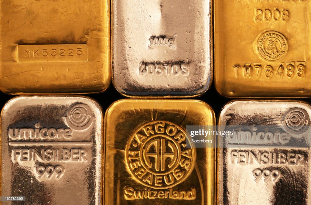 Gold one kilogram bars and silver one kilogram bars are seen in this arranged photograph at Gold Investments Ltd. bullion dealers in London, U.K., on Wednesday, Jan. 15, 2014. Gold futures extended a decline from a one-month high on speculation that the U.S. Federal Reserve will continue reducing stimulus, strengthening the dollar and cutting the metal's appeal as an alternative investment. Photographer: Chris Ratcliffe/Bloomberg via Getty Images