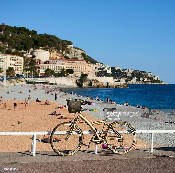 gold painted bicycle- view of Nice beach behind