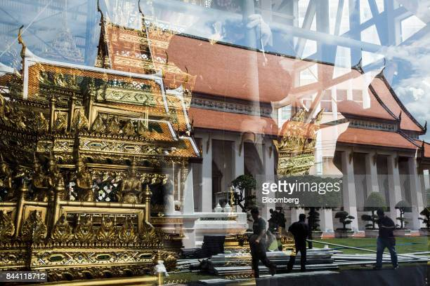A gold palanquin for the cremation ceremony of King Bhumibol Adulyadej sits outside a window reflecting the Bangkok National Museum in Bangkok...