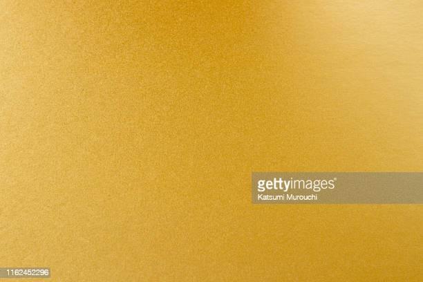gold paper texture background - goldfarbig stock-fotos und bilder