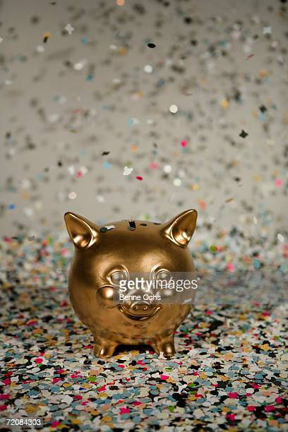 Gold piggy bank amongst floating confetti