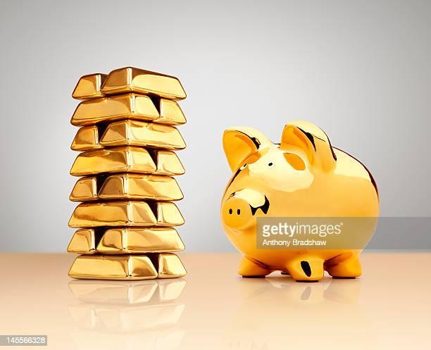 Gold piggy bank beside a stack of ingots