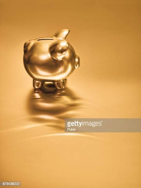 Gold piggy bank on metal background.