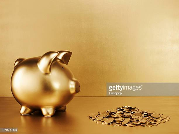 Gold piggy bank with a pile of gold coins