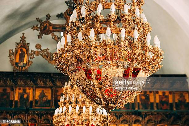 Gold plated old chandelier with two-headed eagle silhouette at little christian church, Cyprus
