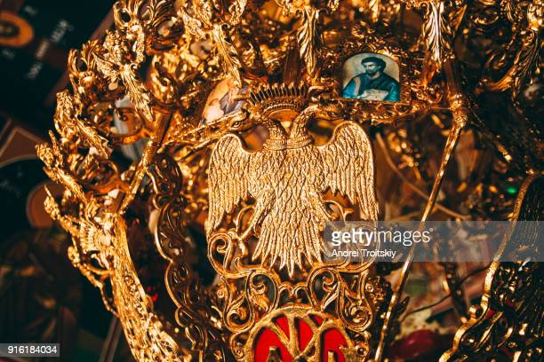 Gold plated old chandelier with two-headed eagle silhouette at little christian church, Greece