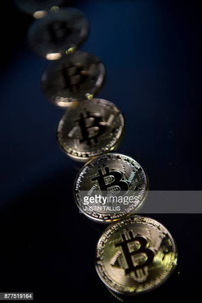 Gold plated souvenir Bitcoin coins are arranged for a photograph in London on November 20 2017 Bitcoin a type of cryptocurrency uses peertopeer...