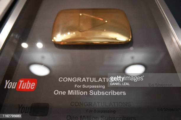 A gold play button awarded to British musician Ed Sheeran for achieving 'one million subscribers' on YouTube is pictured during a press preview of...