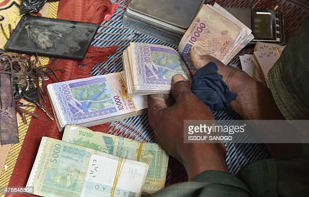 A gold prospector counts money in the craft village of the city of Agadez northern Niger on May 31 2015 AFP PHOTO / ISSOUF SANOGO