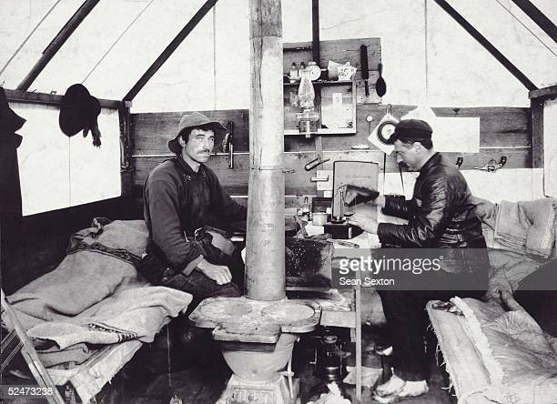 A gold prospector weighing out his partner's share of gold dust in their cabin in Nome Alaska during the gold rush of 1900