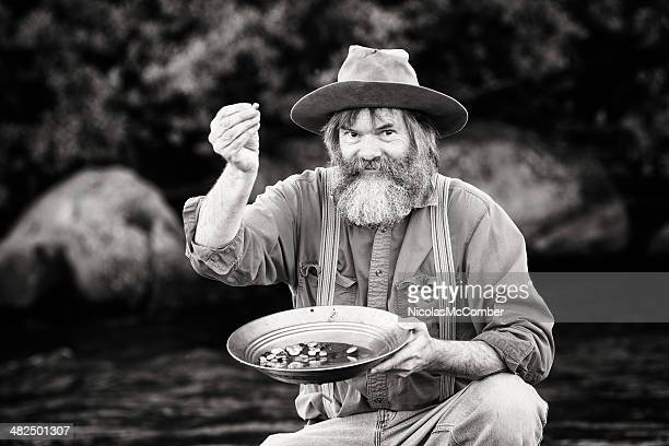 gold rush prospector showing off his nuggets - gold rush stock photos and pictures
