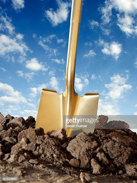 Gold shovel in freshly dug dirt with blue sky