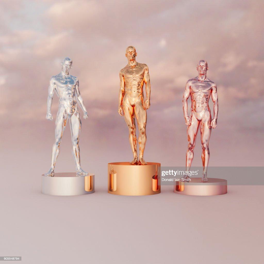Gold, silver and bronze men on pedestals : Foto de stock