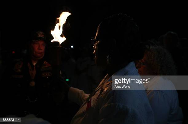 Gold Star Mothers read out the names of their lost loved ones during a candlelight vigil at the Vietnam Veterans Memorial May 26 2017 in Washington...