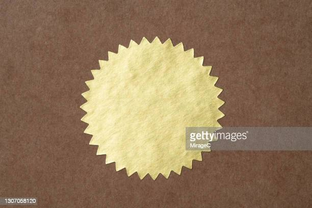gold starburst shaped seal sticker - sale stock pictures, royalty-free photos & images