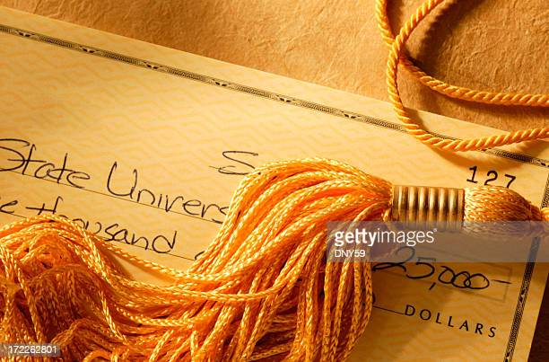 gold tassel on a check written for college tuition - tassel stock pictures, royalty-free photos & images