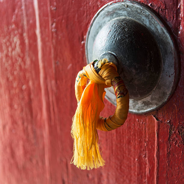 Gold tassel tied to a doorknob on a red door