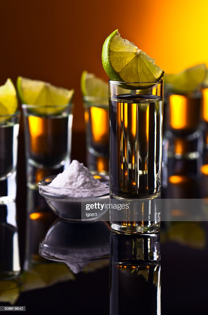 Gold tequila on a black reflective background : Stock Photo