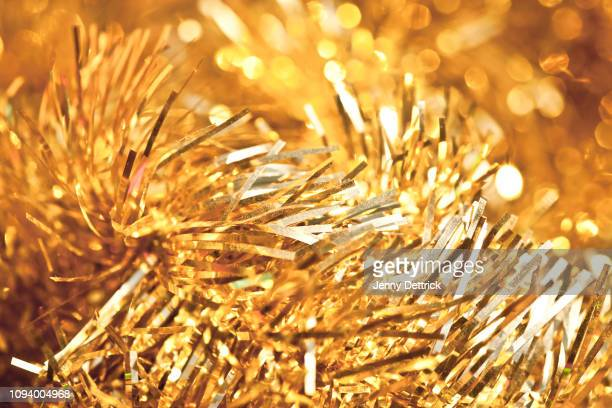 gold tinsel - tinsel stock pictures, royalty-free photos & images