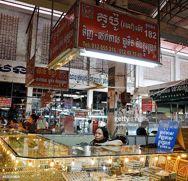 A gold trader waits for customers at her shop in a wet market on November 26 2013 in Siem Reap Cambodia Cambodian continues their daily life despite...