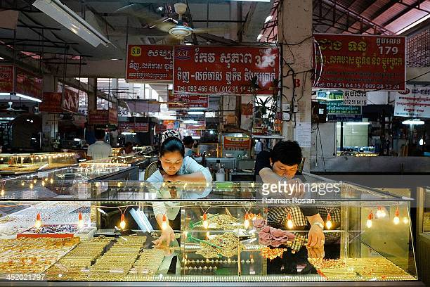 Gold traders arrange gold accessories at their shop in a wet market on November 26 2013 in Siem Reap Cambodia Cambodian continues their daily life...