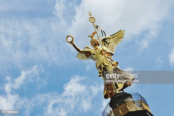 gold victoria sculpture on top of berlin victory column against sky - roman goddess stock pictures, royalty-free photos & images