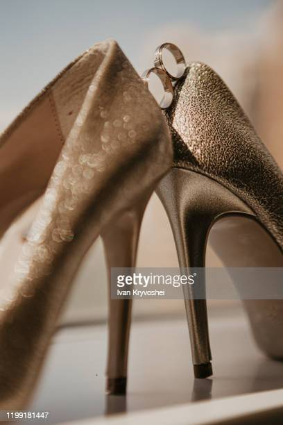 gold wedding rings between pair of golden high heel shoes. wedding details on mirror floor near panoramic window. close up. macro. on sunshine - gold shoe stock pictures, royalty-free photos & images