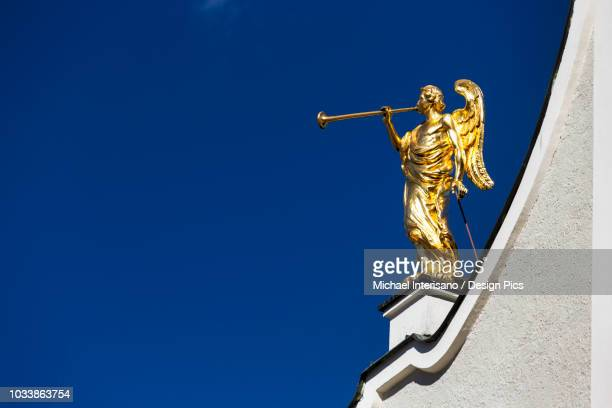 Gold winged angel sculpture with trumpet on top of white church against a blue sky