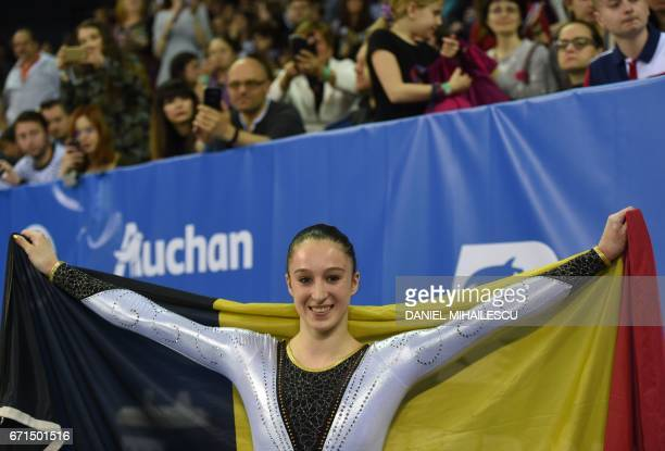 Gold winner Nina Derwael of Belgium poses with a flag after women uneven bars apparatus final at the European Artistic Gymnastics Championship in...