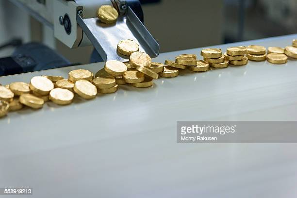 Gold wrapped chocolates on production line in chocolate factory