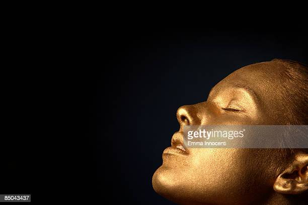 gold young woman  with eyes closed - body paint stock pictures, royalty-free photos & images
