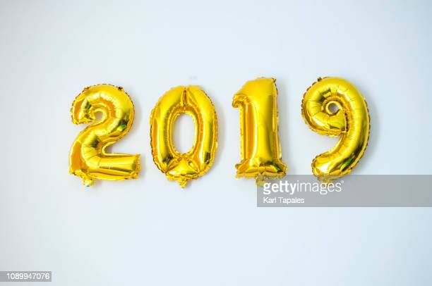 a gold-colored 2019 inflated balloon - 2019 stockfoto's en -beelden