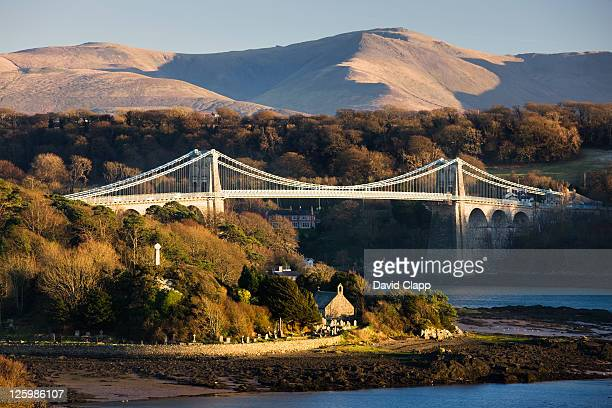 golden afternoon light at the menai bridge that spans the menai strait, the water that separates wales from the island of anglesey, north wales, uk - menai bridge - fotografias e filmes do acervo