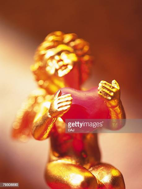 Golden angel holding pink heart, front view, soft focus