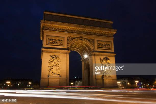 golden arches, arc de triomphe with car trace at night - geometrical architecture stock photos and pictures