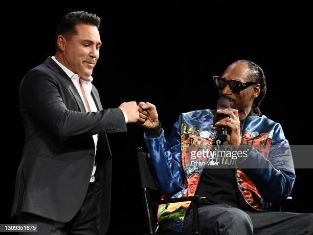 Golden Boy Promotions Chairman and CEO Oscar De La Hoya is greeted onstage by rapper Snoop Dogg during a news conference for Triller Fight Club's...